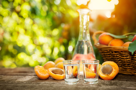 Shot glass with homemade fruit brandy and apricots on the table