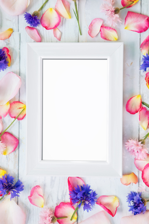 White empty frame with petals around frame on wooden background
