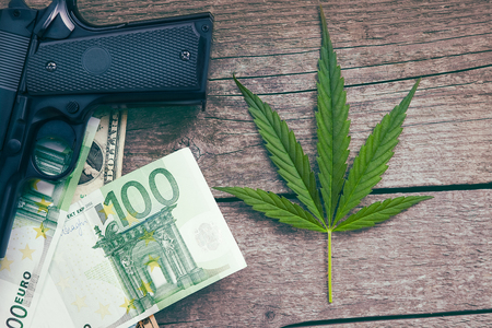 Cannabis leaf with euro bills and gun on wooden background