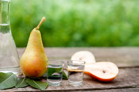 Fruit brandy in shot glass with pear on the table