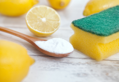 Organic cleaners, lemon and baking soda in wooden spoon on wooden table