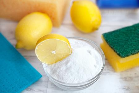 Baking soda, lemon, sponge and dishtowel on wooden table