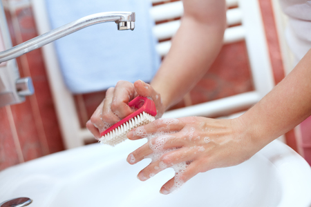 Hand cleaning with brush in bathroom. Hand washing with brush. Imagens