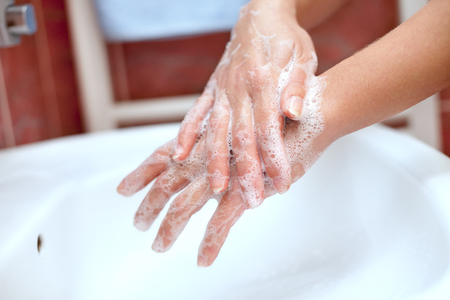 Soapy hands cleaning above the sink. Hand cleaning with soap.