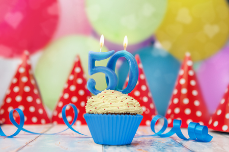 Birthday cupcake for 50 anniversary candle with party hats and balloons Stock Photo - 100984506