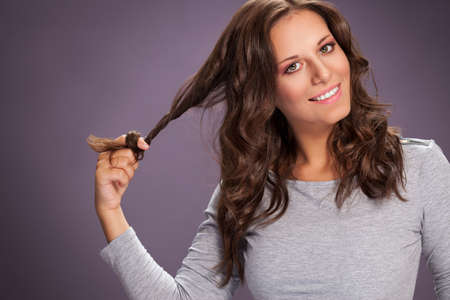 Beautiful young brunette curling her long healthy hair with finger Archivio Fotografico