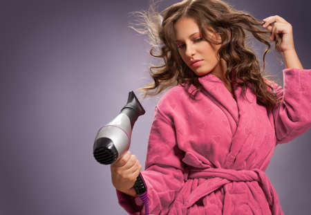 Hair care.Young woman using hair dryer for hair. Archivio Fotografico