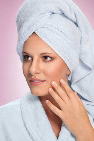 Beautiful young woman in bathrobe touching her face. Skincare and healthy skin concept.