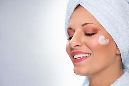 Smiled woman with skin cream in heart shape on face. Skin care treatment.