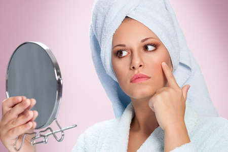 Woman in bathrobe holding mirror and looking her skin
