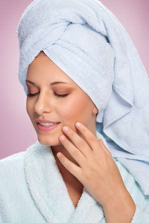 Beautiful spa woman in bathrobe posing with her eyes closed