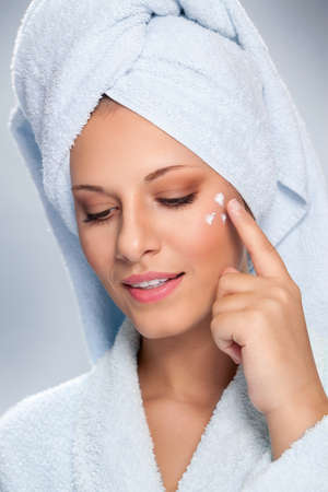 Young woman applying cosmetic cream on a clean fresh face, skincare concept.