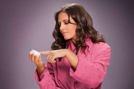 Beautiful woman taking skin cream with finger Archivio Fotografico