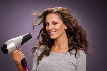Beautiful smiling woman blow drying her long wavy hair