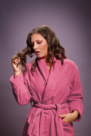 Young woman in bathrobe looking at her damaged hair Stock Photo
