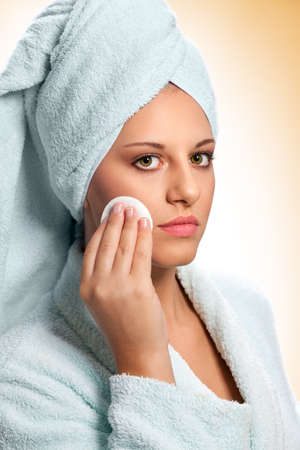 Young woman in bathrobe removing makeup with cotton pads Foto de archivo