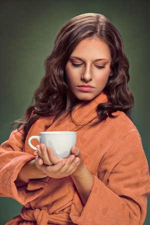 Beautiful woman in bathrobe holding cup with tea Foto de archivo