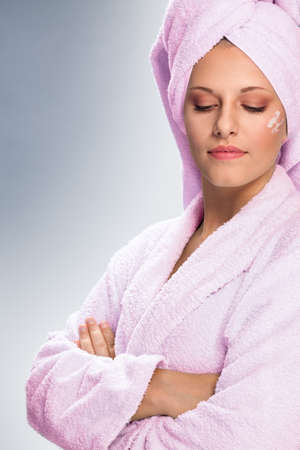 Young woman in bathrobe with skin cream on face