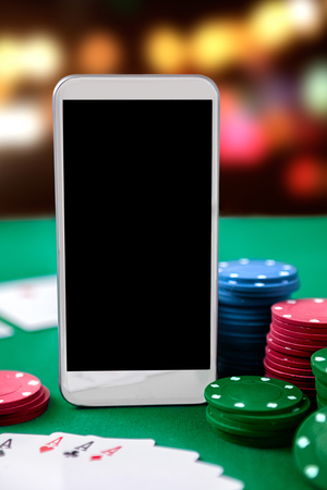 Online casino. Smartphone and chip cards. Online poker game.