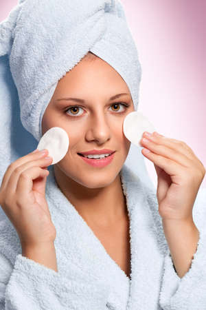Woman in bathrobe holding cotton pads for skin cleaning Foto de archivo