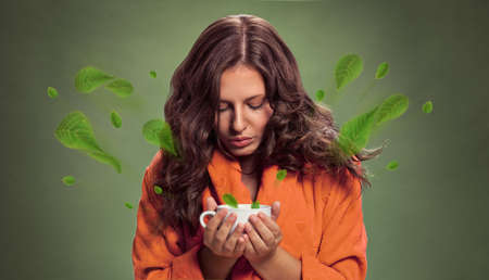 Beautiful young woman holding cup of tea, relaxation drink
