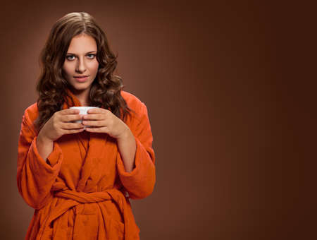 Young brunette woman with coffee cup in hand