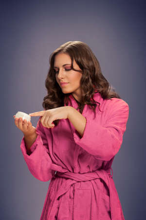 Young woman taking cream for skin with finger
