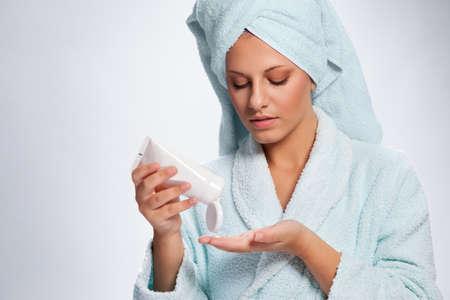 Beautiful young woman applying moisturizing hand cream on her hands