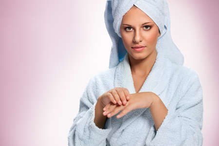 Young woman in bathrobe moisturizing hands with cream