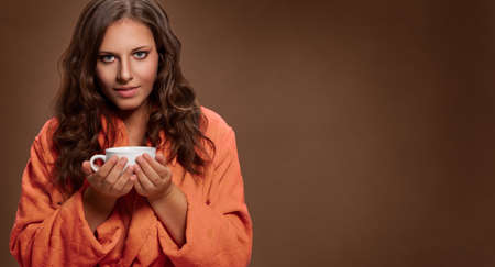 Young brunette woman holding coffee in hand