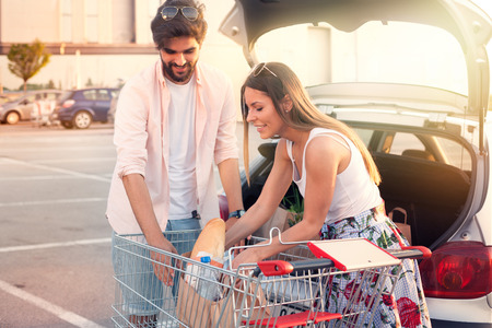 Young couple putting shopping into back of car front of supermarket