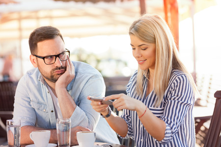 Internet addiction. Attractive woman messaging online via social networks while sitting at cafe with her boyfriend who is having unhappy and bored look Standard-Bild - 103275678