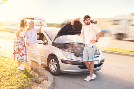 Young man in problem with broken car, while he's worried, his friends make selfie Standard-Bild - 103275681