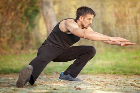 Young muscular man runner stretching legs before running, workout in nature Standard-Bild - 103275687