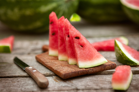 Watermelon slices on chopping board with knife on wooden table Standard-Bild - 103275690