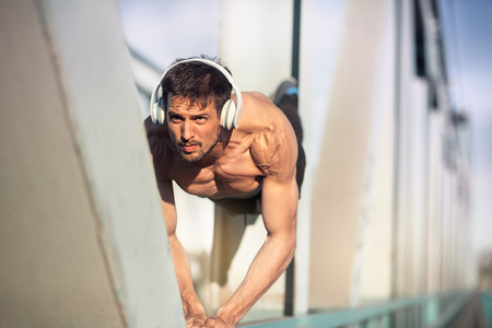 Fit shirtless male doing push-ups, crossfit exercise outdoor, healthy lifestyle concept. Standard-Bild - 103275693