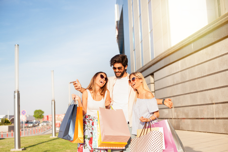 Rich young man with two girls and lot of colored shopping bags and laughing in mall, concept of consumerism, sale, rich life. Standard-Bild - 103275724