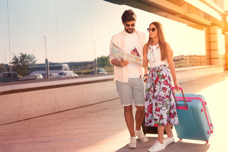 Happy couple with suitcases and map in airport Standard-Bild - 103275734