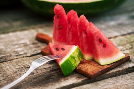 Watermelon slices on cutting board with fork in watermelon Standard-Bild - 103275763