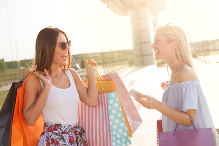 Two young satisfied shopaholic front of shopping mall smiling and talking Stock Photo