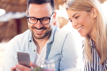 Young couple using phone in coffee shop Standard-Bild - 103275779