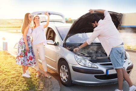 Two carefree girls make selfie, while a man repairs their broken car