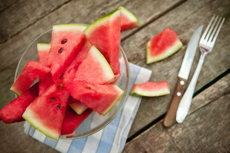 Watermelon cuts in glass bowl and cutlery on the side.Top view. Standard-Bild - 103275803