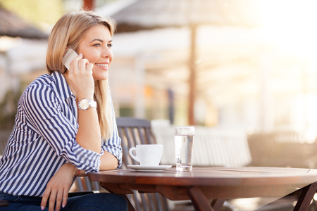 Beautiful busy woman phoning and drinking morning coffee in cafe on morning sun Standard-Bild - 103275809