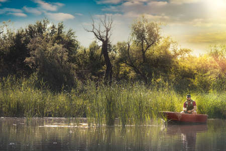 Fisherman in wooden boat catching fish on the lake, fishing concepts.