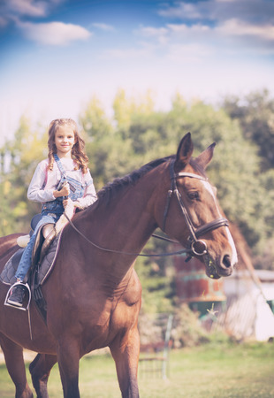 Little blond girl reading horse on farm
