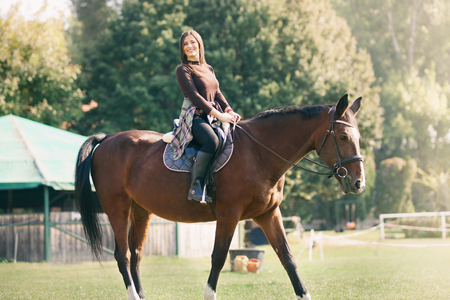 Beautiful girl riding a horse in countryside, happy woman