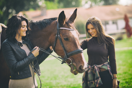 Beauty women veterinarian and owner enjoying with a horse outdoors at ranch. Stok Fotoğraf