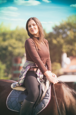 Young woman enjoying a horse ride on a sunny day, happy woman on horseback Фото со стока