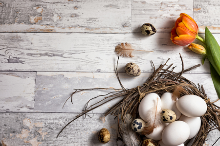 Quail and chicken eggs in a rustic nest on a wooden board